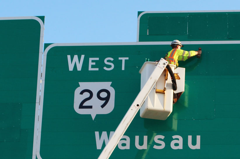 Image of man working on a highway sign